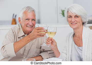 Elderly couple toasting with white wine in kitchen