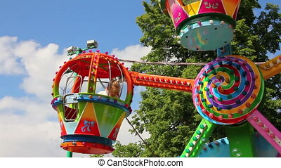 children ride on the carousel in the park