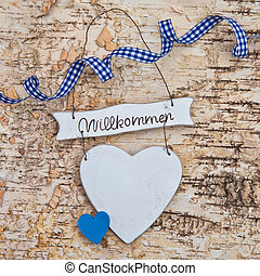 Heart with welcome written in german on a wooden background...