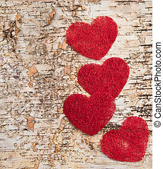 Red hearts on wooden background - Four red hearts on a...