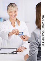 Insurance card - Cheerful young doctor giving insurance card...