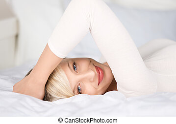 Attractive woman posing with hands on her head in bedroom