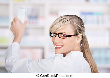 Friendly female pharmacist stores the medicines - Friendly...