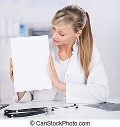 Medical doctor shows white blank paper with stethoscope on...