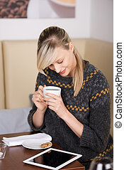Woman reading an e-book in a cafe sitting at a table with a...