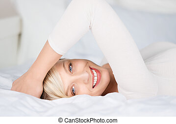 Lying female - Beautiful young woman lying on bed in a close...