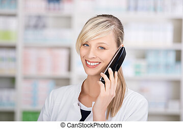 Smiling female pharmacist on the phone