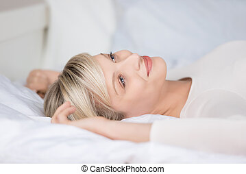 Attractive female relaxing on her bed in a close up shot