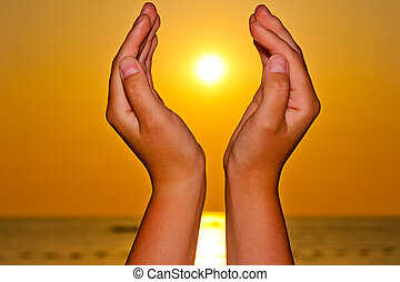 Sun over the sea in female hands
