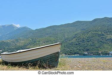 rowing boat - a rowing boat perched on a pebble beach