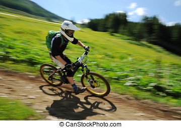 Downhill bike racer - Single biker in the countryside racing...