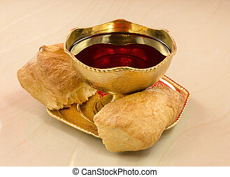 Ancient golden chalice with red wine and bread broken into...