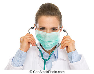 Doctor woman in mask using stethoscope