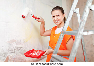 painter paints wall with roller - Female house painter...
