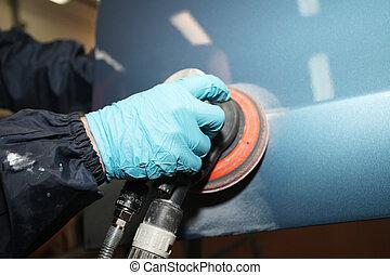 polishing - Painter polishs a car body component