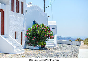 Beautiful paved street with old traditional white house in Fira, Santorini, Greece