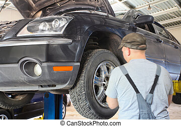 mechanic repairing a car - Image of a mechanic repairing a...