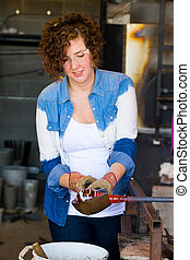 Woman Glassblower - A female is blowing glass and using a...