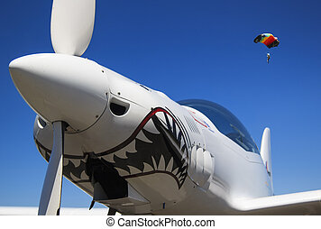 nose and propeller of a white aeroplane in a blue sky and a parachute