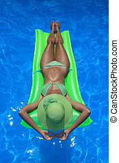 Woman lying on an air mattress in blue pool