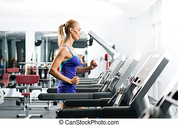 attractive young woman runs on a treadmill, is engaged in...