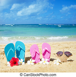 Flip flops and starfish with sunglasses on sandy beach -...