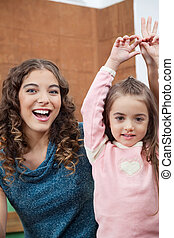 Teacher And Little Girl With Hands Raised In Classroom