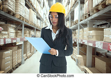 indian woman doing stock tick on warehouse , with safety...