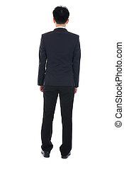 back view of Business man looks ahead. Young guy in black suit watching.Isolated over white background