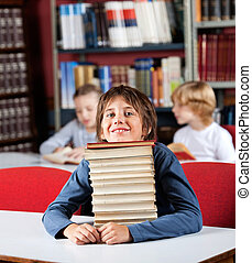 Schoolboy Resting Chin On Stack Of Books At Table In Library...