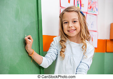 Cute Girl Writing On Board In Kindergarten - Portrait of...