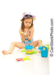 Girl using sunblock lotion and sitting down with beach toys...