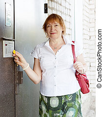 woman opens door with electronic key - Mature woman opens...