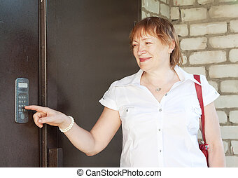 woman using intercom outdoor - Mature woman using house...