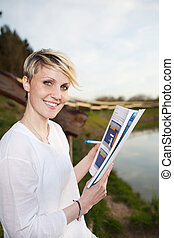 Young Smiling Woman Working By The Lake - Smiling young...