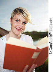 Young Blond Woman Reading Book By Lake - Smiling young...