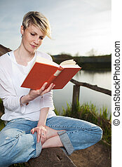 Blond Woman Reading Book By Lake - Young beautiful woman...