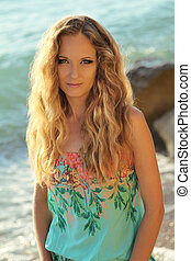 Beautiful woman with wavy hair on sea beach background, outdoors portrait