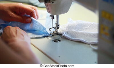 Seamstress sews childrens clothes on machine, close-up
