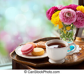 Cup of coffee with macaroons on a table with flowers...