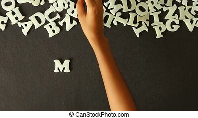 Monday - A person spelling Monday with Plastic letters