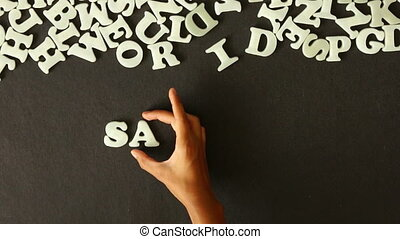 Saturday - A person spelling Saturday with Plastic letters