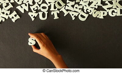 Sunday - A person spelling Sunday with Plastic letters