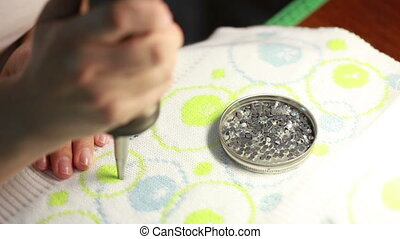 Woman sticking sequins on knitted fabric, close-up