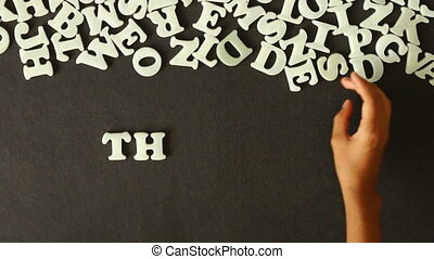 Thursday - A person spelling Thursday with Plastic letters