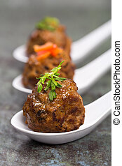 Asian meatballs, garnished with pea shoots and red pepper...