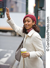 Woman Hailing A Cab - A pretty young business woman hails a...