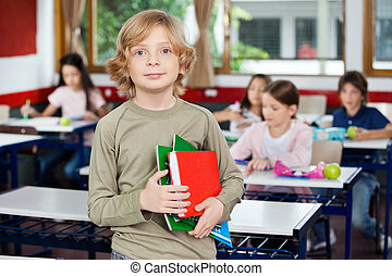 Schoolboy Holding Books While Standing In Classroom -...