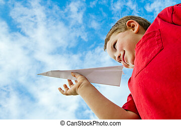 Child playing with paper airplane