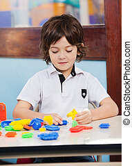 Boy Playing With Blocks In Classroom